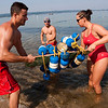 Record-Eagle/Douglas Tesner<br /> Traverse City lifeguards, from left, Ben Sattler, Sean Seekins and Danielle Beaudoin bring in the swimming area floats at Bryant Park Beach. Labor Day marked the last day the beaches in the area had lifeguards for the season.