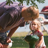 Record-Eagle/Douglas Tesner<br /> Elyse Brayton, 3, helps her father Matt Brayton get a drink from a water fountain at Traverse City State Park Monday afternoon.