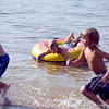 Record-Eagle photo/Jan-Michael Stump<br /> Connor Whyte, 7, of Rockford floats in a tube while his cousin Nathan Lawson, 8, of Traverse City and brother Camden Whyte, 5, run out of the water at the Traverse City State Park beach on Grand Traverse Bay's east arm.