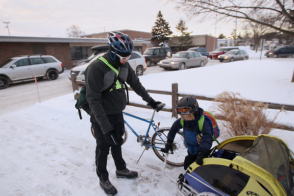 Record-Eagle/Keith King<br /> Ross Hammersley, of Traverse City, stands nearby as his son, Emerson Hammersley, 6, exits a bike trailer he was riding in Wednesday, February 6, 2013, as Ross drops him off at school. Afterward, Ross continued riding his bike to work.