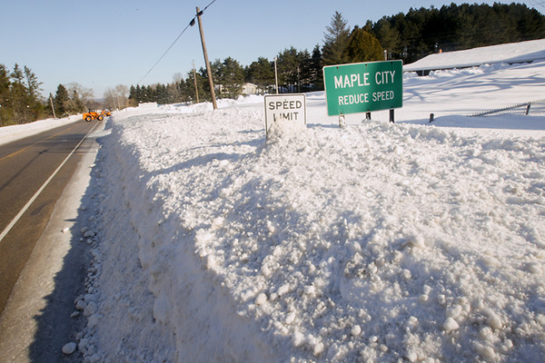Record-Eagle/Keith King<br /> A front-end loader, back left, moves snow on South Maple City Road in Kasson Township.