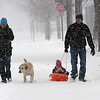 Record-Eagle/Douglas Tesner<br /> Abby and Sam Porter walk down a street heading to a friend's house with their daughter, Mae, 2, in tow on a sled, and their dog Roy during Sunday;s snow storm.