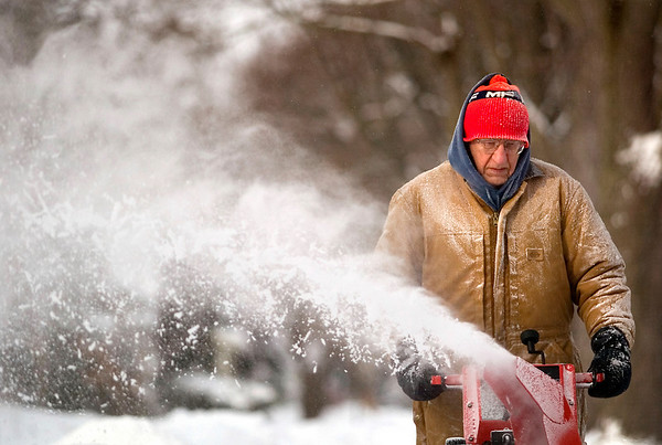 """Record-Eagle/Jan-Michael Stump<br /> Dick Emerson snowblows the sidewalk outside his and his neighbors' homes on 11th Street on Thursday morning. """"Been here all my life, you get used to it,"""" he said of the snow."""