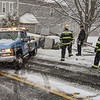 JENN SMITH - THE BERKSHIRE EAGLE<br /> Members of the North Adam Fire Department stand by Monday as operators from Dean's Towing prepare to remove a Chevrolet SUV that crashed into the driveway of 23 Bradley St. in North Adams. The driver said the vehicle began sliding down the snow-covered road when he lost control, drove through a fence, nicked a tree, flipped and landed on the passenger side. Monday, March 23, 2020