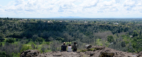A seat with a view-  Park visitors enjoy a partly cloudy sky as they sit looking toward the Sutter Buttes near Monkey Face in Upper Bidwell Park, Chico Calif. Tues. April 18, 2017.  (Bill Husa -- Enterprise-Record)