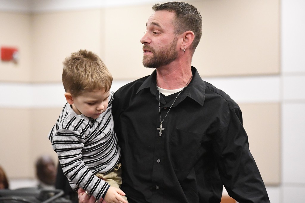 . With his son Jaxon in his arms, James Majkut addresses the courtroom during a judicial release hearing for Adrianna M. Young , Jan. 4, 2018. The 26-year-old Oberlin woman was granted early release, by Lorain County Common Pleas Court Judge James Miraldi, after serving nearly eight months of a 54-month prison term. Young plead guilty, March 9, 2017, to causing the July 28, 2015 death of 34-year-old Debra Majkut, of Amherst Township, and permanently scaring the couple\'s son, who was 5 months old at the time of the crash. (Eric Bonzar�The Morning Journal)