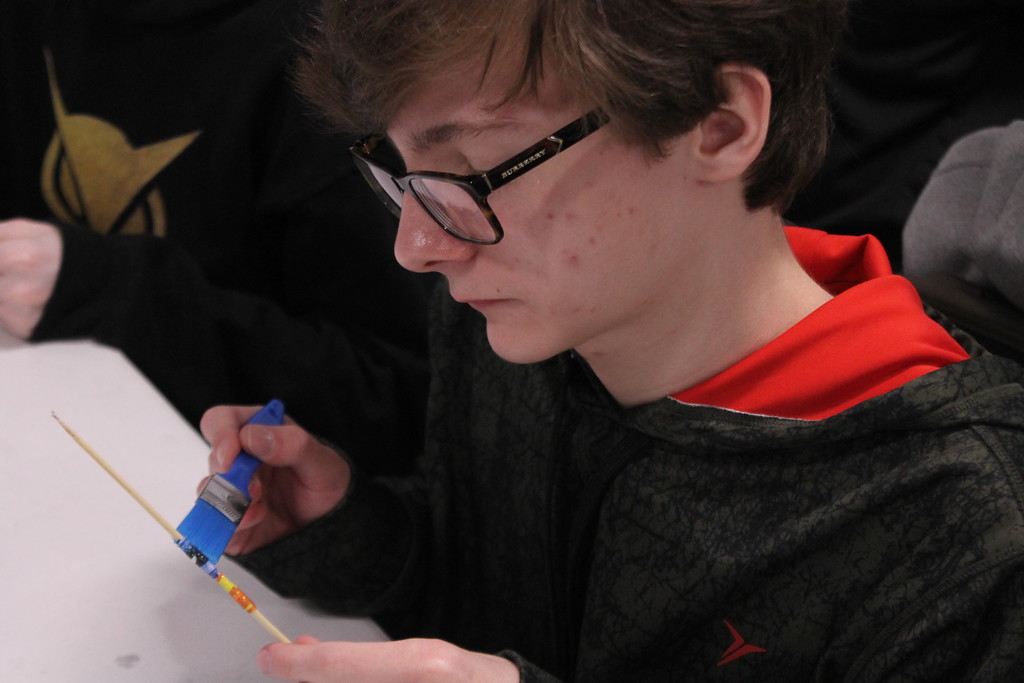 . Kristi Garabrandt � The News-Herald <br> Jacob Haines, 14, puts glitter paint on the paper beads made by some of the eighth grade students for the Earth Day festival during the Ridge Middle School Day of Service on March 27, 2018.