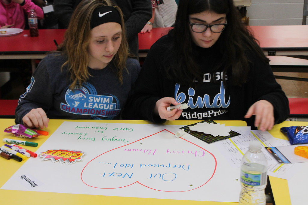 . Kristi Garabrandt � The News-Herald <br> Eighth-grade students Maddie Michalski, 13, and Emma Gaddis, 14, from Ridge Middle School a work together during Ridge Middle School\'s Day of Service on March 27, 2018  to create posters for the April 7, Deepwood Idol Competition.