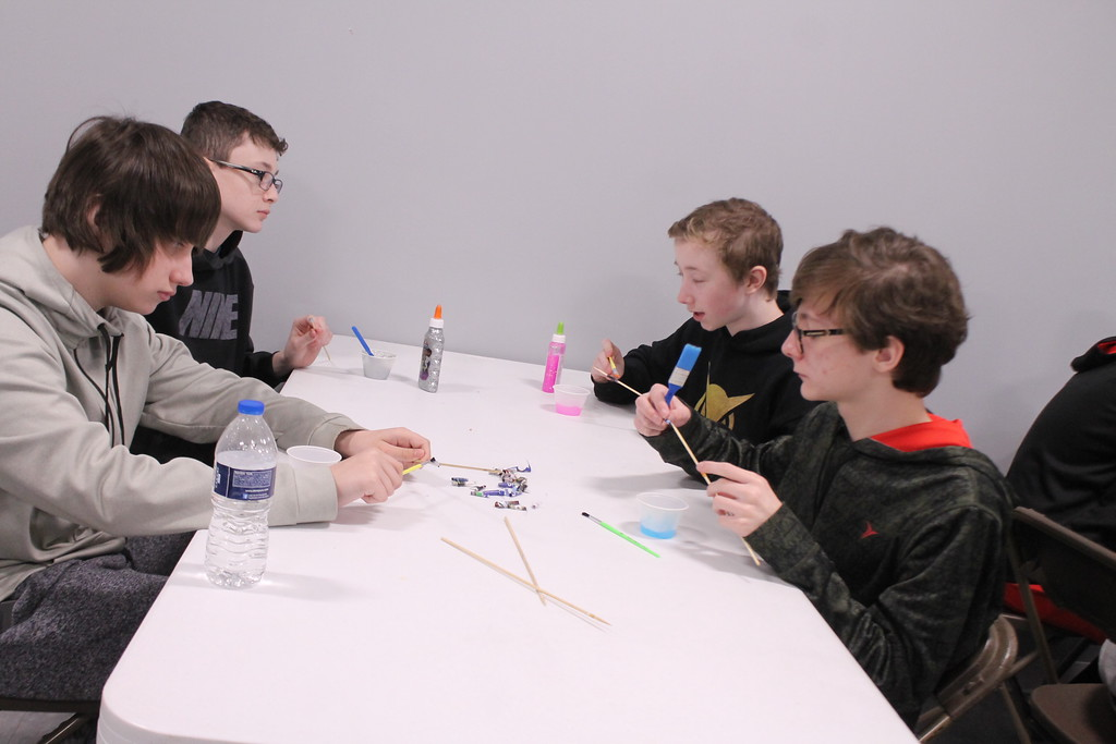 . Kristi Garabrandt � The News-Herald <br> Jack, Sweeney, 13, Spencer Bowen, 14, Josh Walden, 14 and Jacob Haines, 14, put glitter paint on the paper beads made by some of the eighth grade students for the Earth Day festival during the Ridge Middle School Day of Service on March 27, 2018.