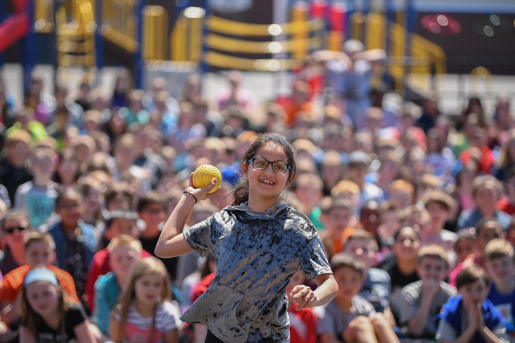 . Eric Bonzar�The Morning Journal. Nine-year-old fourth-grader Mia Khandekar tosses a ball and tries to dunk Assistant Superintendent Ben Hodge in a dunk tank, during Avon Heritage Elementary School\'s special assembly to close out Autism Awareness Month, April 30, 2018.