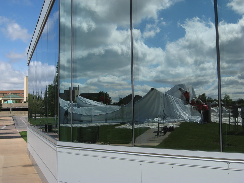 Richard Payerchin - The Morning Journal <br> The glass windows of the Lorain Port Authority office building, 319 Black River Lane, reflect the crew from Aable Rents setting up the canopy over the stage at Black River Landing, Lorain's waterfront festival site, on May 3, 2017. Erecting the canopy signals the unofficial start of summer, or at least the start of preparation for summer, at Black River Landing.