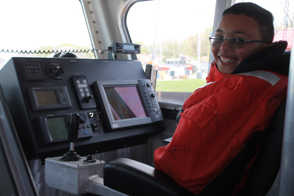 . Charlie Beardslee, 11, Fairport, assists with driving  the  Coast Guards 45\' foot response boat during the USCG Fairport Station Open House,  May 19.  Kristi Garabrandt - The News-Herald