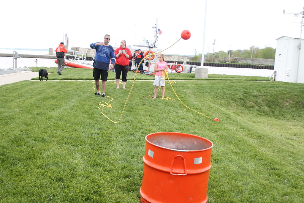. Matt Bochnik, Mentor and his step-daughter Sierra Cook, 9,  try to toss a ball on the end of a rope in the barrel to simulate tossing a life preserve to a person in the water during the USCG Fairport Station Open House May, 19