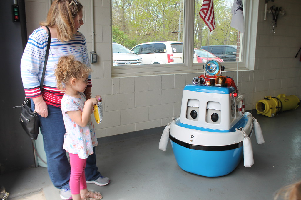 . Laurie Smith , Concord looks on as her granddaughter Liberty Smith, 4,    talks with Coastie the Tug Boat, The Coast Guards remote controlled robotic cartoon character that is intended to teach kids about water safety during the USCG Fairport Station Open House,  May 19.  Kristi Garabrandt - The News-Herald