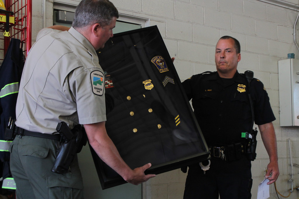 . Kristi Garabrandt � The News-Herald <br> Eastlake Police Chief Larry Reik presents retiring Sergeant Chris Gutka with his dress uniform and awards in a shadow box during the retirement party held at Eastlake Fire Department on May 25, Gutka retired after 22 years with the department.