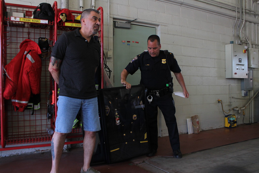 . Kristi Garabrandt � The News-Herald <br> Eastlake Police Chief Larry Reik presents retiring Lieutenant Robert Gonzalez with his dress uniform and awards in a shadow box during the retirement party held at Eastlake Fire Department on May 25, Gonzalez retired after 29 years with the department.