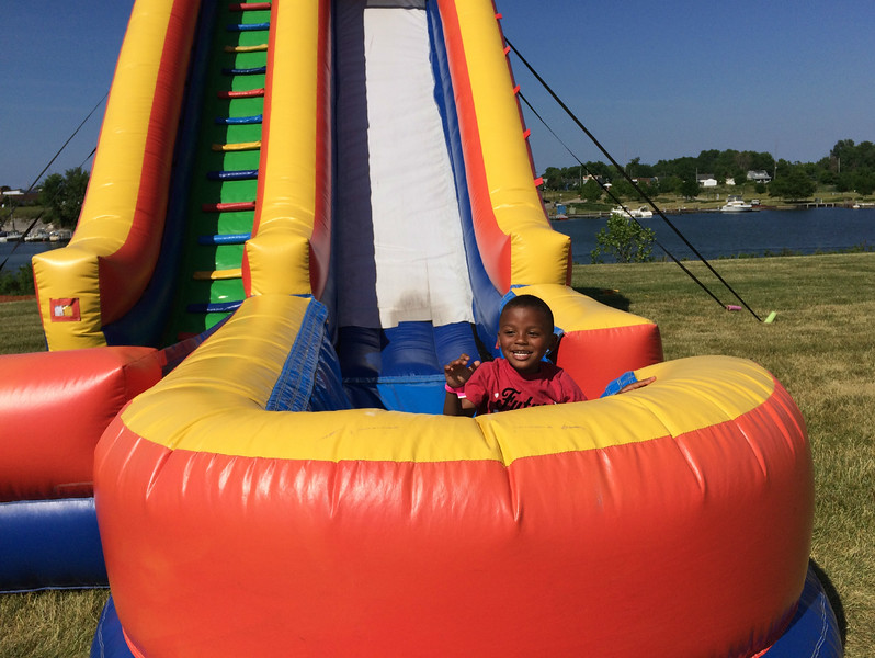 Carol Harper - The Morning Journal <br> Victor McCall, 4, smiles at his mother, Gabrielle Massey, 27, Akron, after he jumped from the top of the slide and tumbled down on June 25, 2016, at Lorain International Festival at Black River Landing in Lorain.