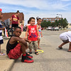 Carol Harper - The Morning Journal <br> Javid West, 8, seated, guards a pile of candy and trinkets June 26, 2016, at Lorain International Festival Parade, while his sister, Zariah, 3, behind him, and twins Jaiden and Jaida Marshall, both three, watch for more parade participants. The group from Elyria included their mothers, Cynthia West, 28, not pictured, and Heather Marshall, 23, behind Zariah.