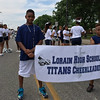 Carol Harper - The Morning Journal <br> Boys support Lorain High School Titans Cheerleaders by carrying a banner during a Lorain International Festival Parade June 26, 2016, on Broadway Avenue in Lorain.
