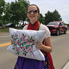 Carol Harper - The Morning Journal <br> A girl shows handiwork while wearing a traditional costume June 26, 2016, during a 50th Anniversary Lorain International Festival Parade on Broadway Avenue in Lorain.