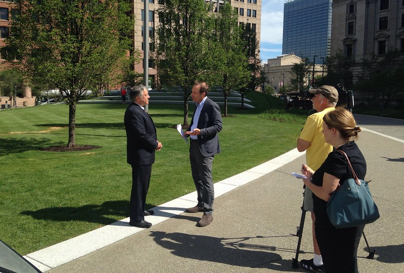 Cuyahoga County Executive Armond Budish doing a TV interview with Public Square's Concert Hill as backdrop.