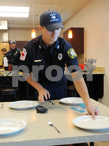 copyright 2012 Sarah A. Miller/Tyler Morning Telegraph  Firefighter J.D. Stroud sets the table for lunch at Tyler Fire Station 5 Friday during the taping of a cooking segment for television station Channel 3.