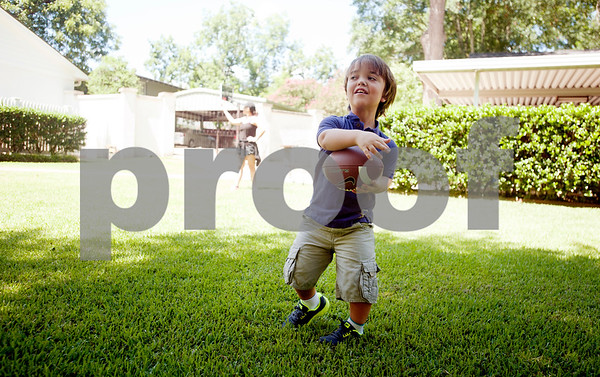 """copyright 2012 Sarah A. Miller/Tyler Morning Telegraph  Aulden Love, 11, of Henderson, plays catch with his dad Greg (not pictured) at their home July 18. Love has achondroplasia, a type of dwarfism, and stands at 3'8"""". He enters the sixth grade this fall."""