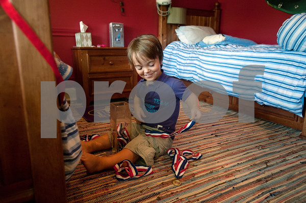 "copyright 2012 Sarah A. Miller/Tyler Morning Telegraph  Aulden Love, 11, of Henderson, shows off his collection of medals form various sporting events at his bedroom July 18. Love has achondroplasia, a type of dwarfism, and stands at 3'8"". He enters the sixth grade this fall."