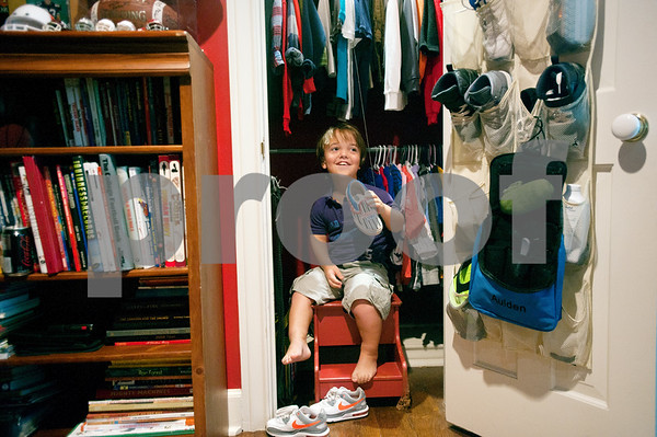 """copyright 2012 Sarah A. Miller/Tyler Morning Telegraph  Aulden Love, 11, of Henderson, shows off some of his tennis shoes that he collects in his bedroom July 18. Love has achondroplasia, a type of dwarfism, and stands at 3'8"""". He enters the sixth grade this fall."""