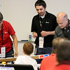 Jonathan Tressler - The News-Herald. Avery Dennison employees, from left, Molly Waters, senior regional technical specialty, Edward Khodaei, quality engineering technologist, and Mark Baierl, senior dvisional quality engineer, set up their S.T.E.M. education kit during a collaboration between the company and Partners in Science Excellence Aug. 9