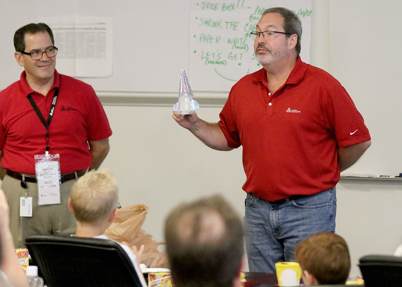 Jonathan Tressler - The News-Herald. Avery Dennison technical leader Rick Bertone, left, smiles as colleague Greg Brumbaugh, a senior technical leader, explains their team's S.T.E.M. education kit Aug. 9 at the company's faciity on Norton Parkway in Mentor.