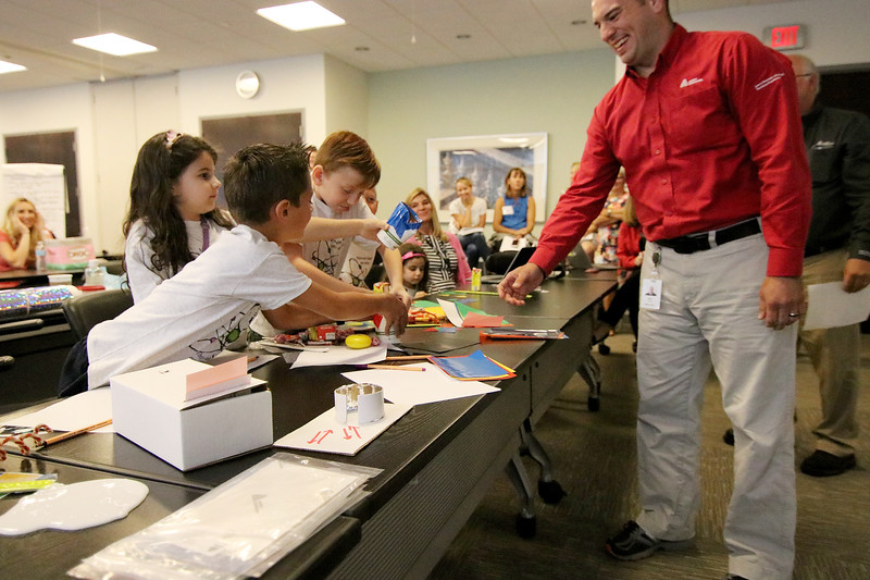 Jonathan Tressler - The News-Herald. At right, Mike Wilson, an Avery Dennison application consultant, smiles as a group of elementary school partcipants react to his team's S.T.E.M. project kit Aug. 9 during a collaboration between the company and Partners in Science Excellence.