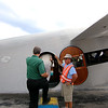 Jonathan Tressler - The News-Herald. EAA volunteer Tim Niederkorn helps passengers board the Ford Tri-Motor aircraft visiting Lost Nation Airport through Aug. 12 in this Aug. 10 photo.