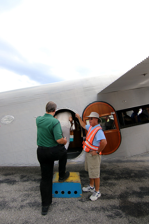 . Jonathan Tressler - The News-Herald. EAA volunteer Tim Niederkorn helps passengers board the Ford Tri-Motor aircraft visiting Lost Nation Airport through Aug. 12 in this Aug. 10 photo.