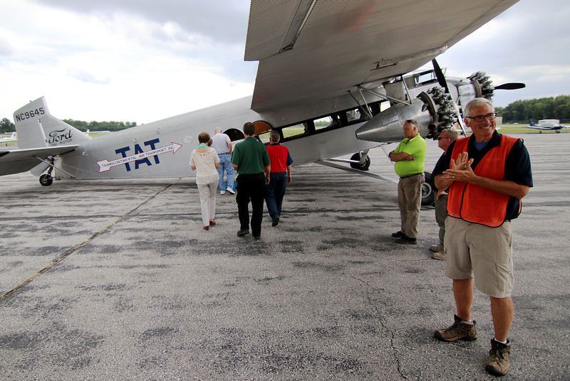 Jonathan Tressler - The News-Herald. EAA volunteer Linn Obery, far right, looks as excited as the soon-to-be passengers boarding the Ford Tri-Motor aircraft at Lost Nation Airport through Aug. 12.
