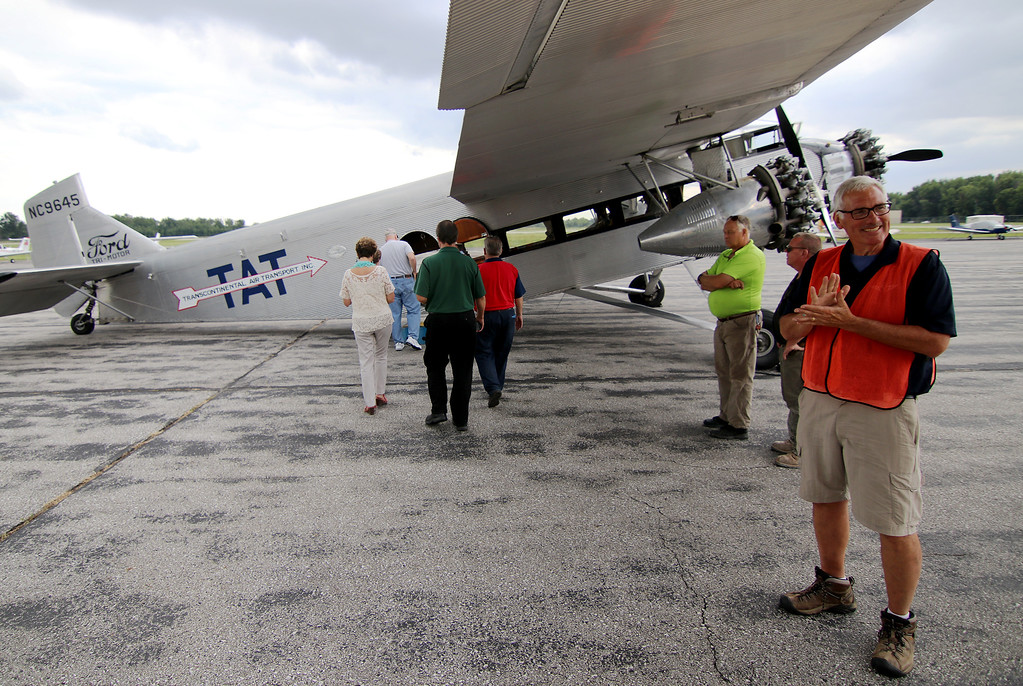 . Jonathan Tressler - The News-Herald. EAA volunteer Linn Obery, far right, looks as excited as the soon-to-be passengers boarding the Ford Tri-Motor aircraft at Lost Nation Airport through Aug. 12.