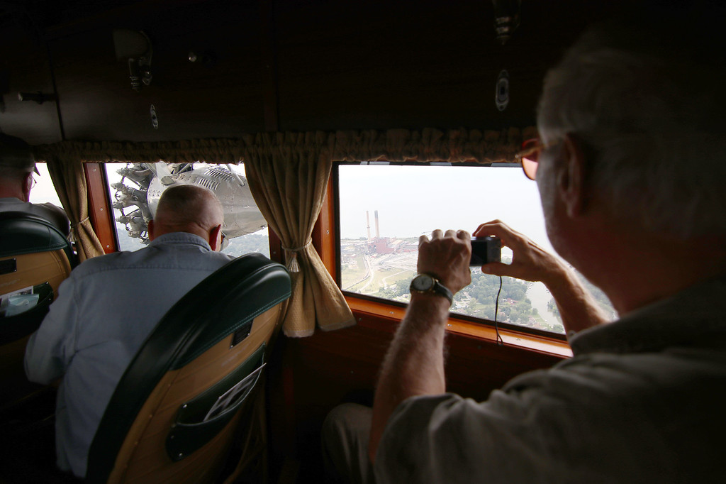 . Jonathan Tressler - Passengers aboard the Ford Tri-Motor plane visiting Northeast Ohio through Aug. 13 snap photos and enjoy a rare view of the Eastlake power plant from a 1928 vintage aircraft in this Aug. 10 photo.