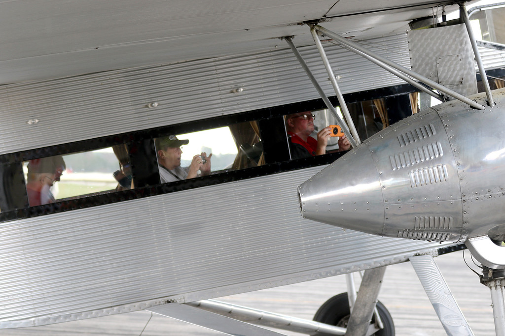 . Jonathan Tressler - The News-Herald. Some happy passengers aboard the Ford Tri-Motor aircraft visiting Lost Nation Airport through Aug. 12 strriking one of the more popular poses while seated inside - the cell-phone snap.