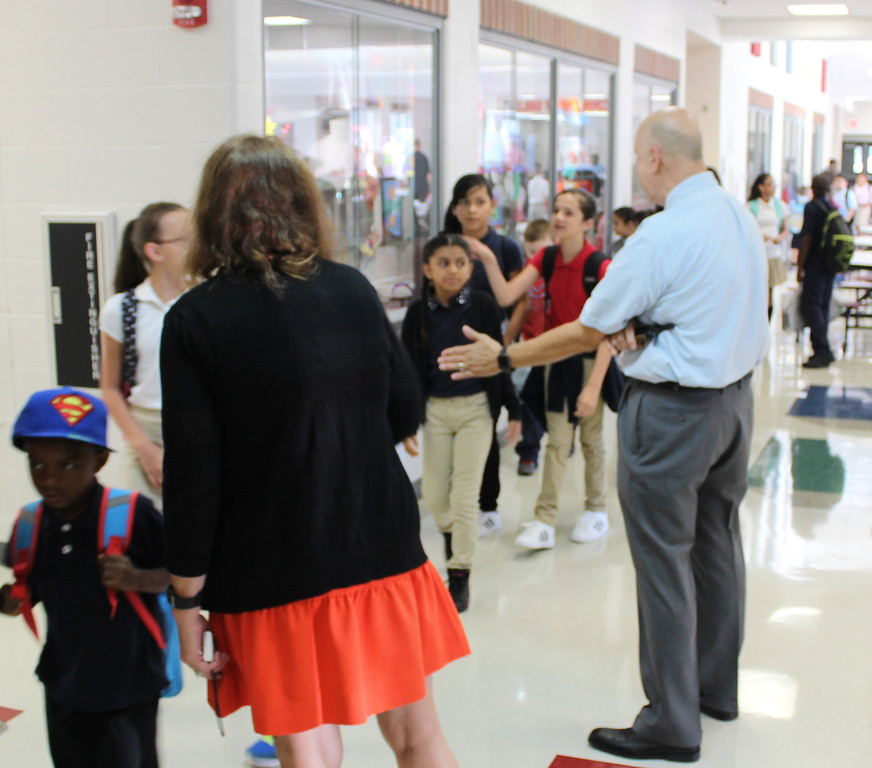 . Painesville Schools Superintendent John Shepard, right, and fifth-grade paraprofessional Cecilia Sullivan, foreground, greet Chestnut Elementary School students on the first day of school, Aug. 16, 2017. (Tawana Roberts - The News-Herald)