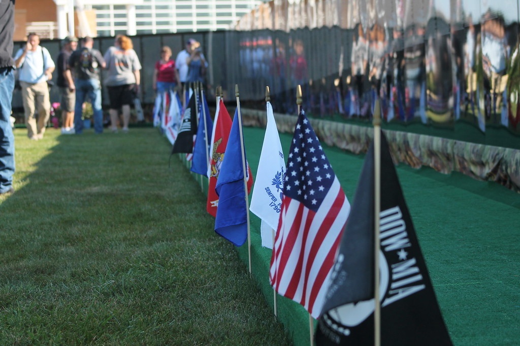 . Kristi Garabrandt � The News-Herald <br> Flags representing the United States, Pow*MIA (Prisoners of War*Missing in Action) and the  military branches line the Moving Wall at Perry High School. Sept. 21.