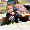 BEN GARVER — THE BERKSHIRE EAGLE<br /> David Dickerman , a first grader at at Morningside Elementary School in Pittsfield, makes a necklace in Danielle Oldread's class for the 100th day of school. The necklaces are made from 100 pieces of fruity cereal pieces.