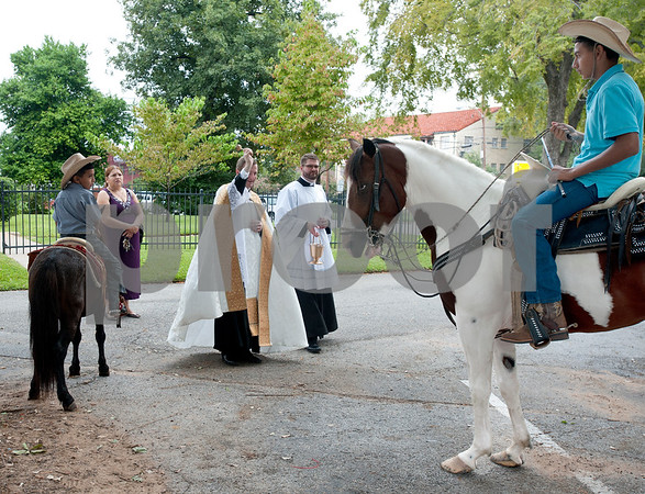 photo by Sarah A. Miller/Tyler Morning Telegraph  Father Anthony McLaughlin, rector of Cathedral of the Immaculate Conception and deacon Matthew Stehling bless Angel Zavala Jr.'s horse at St. Gregory Cathedral school's annual pet blessing Thursday in Tyler. Pictured at left are Adrain Zavala, 6, and his mother Mary Zavala.