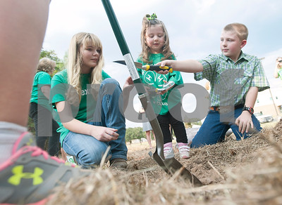 Audrey Stanley, 15, of Lindale, Asa Morgan, 2, of Tyler, and Coy McKenzie, 11, of Tyler, help plant a bur oak tree at Smith County Juvenile Services in Tyler Friday Oct. 9, 2015. The tree planting event was hosted by Smith County 4-H as part of National 4-H Week celebrating the 100th anniversary of 4-H.   (Sarah A. Miller/Tyler Morning Telegraph)
