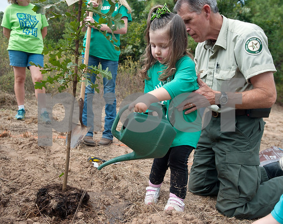 Daniel Duncum staff forester with Texas A&M Forest Service helps Asa Morgan, 2, water a newly planted tree at Smith County Juvenile Services in Tyler Friday Oct. 9, 2015. The tree planting event was hosted by Smith County 4H as part of National 4H Week.   (Sarah A. Miller/Tyler Morning Telegraph)