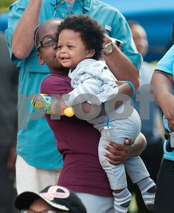 Trinity Curry, 10, holds her infant cousin Justyce Caraway as they watch a praise dance team perform after the annual Community Faith-Based Health Walk to promote living a healthy lifestyle Saturday Oct. 10, 2015 at Woldert Park in Tyler. Nearly 200 people completed the one and a half mile walk starting and ending at the park.  (Sarah A. Miller/Tyler Morning Telegraph)