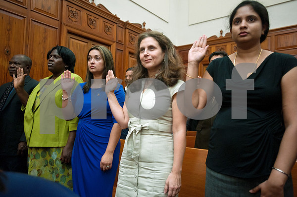 photo by Sarah A. Miller/Tyler Morning Telegraph  United States citizenship candidates raise their hands to take the oath of citizenship during the naturalization ceremony at the U.S. District Courthouse in Tyler Thursday.