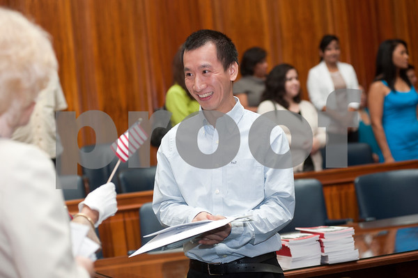 photo by Sarah A. Miller/Tyler Morning Telegraph  Longview resident Ben Xiang Zhu receives an American flag after becoming a United States citizen at the U.S. District Courthouse in Tyler Thursday.