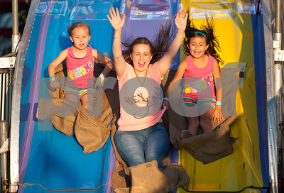 Jaime Viramontes of Lindale rides a slide with her daughters KaileyAnn Viramontes, 5, left, and Karime Viramontes, 8, right, at the East Texas State Fair in Tyler, Texas Thursday evening Oct. 1, 2015. The fair closes Sunday night.  (Sarah A. Miller/Tyler Morning Telegraph)