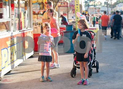 Sisters Emily Arrington, 6, and Aleah Arrington, 9, of Tyler, carry balloon dogs at the East Texas State Fair in Tyler, Texas Thursday evening Oct. 1, 2015. The fair closes Sunday night.  (Sarah A. Miller/Tyler Morning Telegraph)