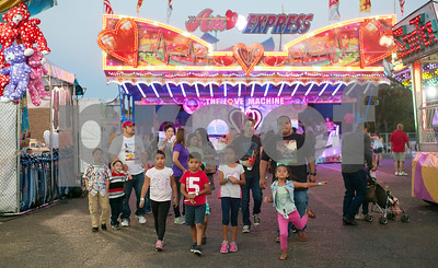 Fairgoers walk through the carnival rides and games at the East Texas State Fair in Tyler, Texas Thursday evening Oct. 1, 2015. The fair closes Sunday night.  (Sarah A. Miller/Tyler Morning Telegraph)